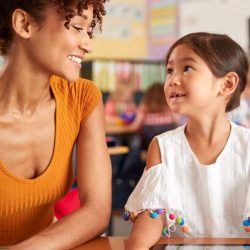 Young Girl Student Smiling Up At Female Teacher