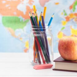 Aws Colored Pencils In Mason Jar Next To Books C Eraser C And An Apple On Top Of A Book