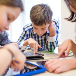 Kids Smiling While Using Tablets At Table