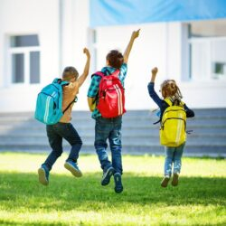 Three Students Jumping With Backpacks In Grass Infront Of School