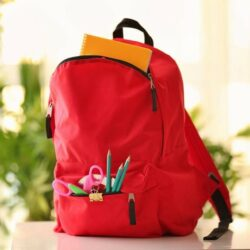 Red Backpack With School Supplies Visible In Pocket