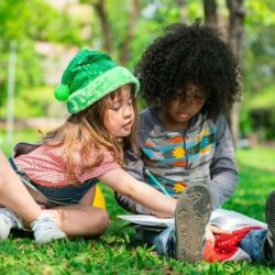 Boy And Girl Student Sitting In Grass Doing Homework