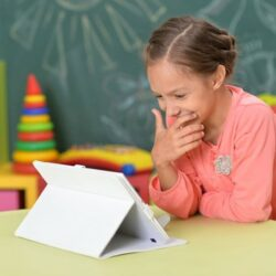 Girl Student Smiling While Viewing Tablet At Table