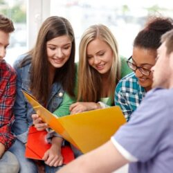 Group Of Students Smiling While Looking In Folder