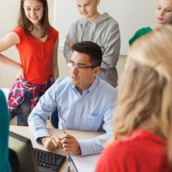 Teen Students Standing Around Male Teacher While Talking