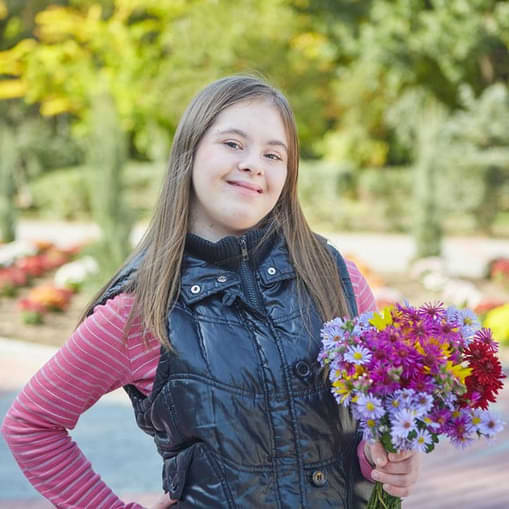 Downsyndrome Girl Holding A Boquet Of Flowers And Smiling