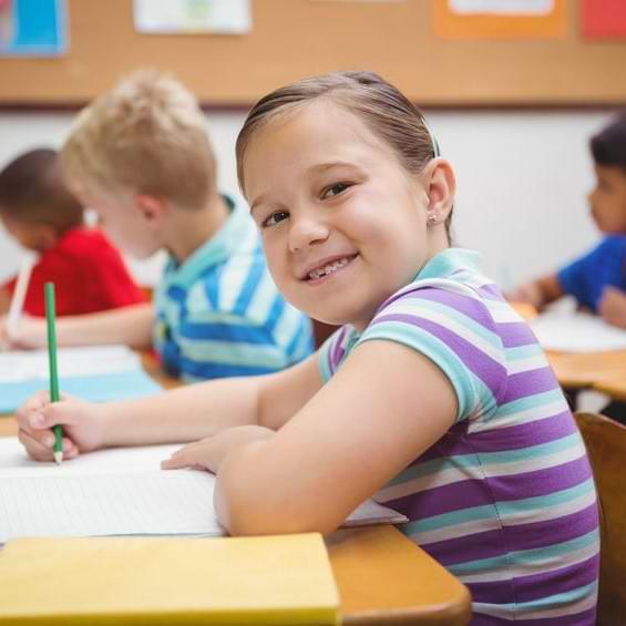 Smiling Female Student At Desk C Writing