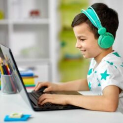 Young Boy With Headphones On While Using Laptop