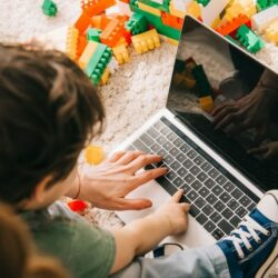 Mother And Small Child Using Laptop On The Ground With Toy Blocks Around Them
